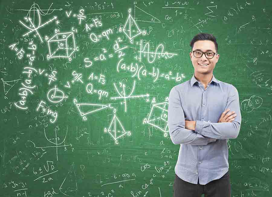young man smiling beside complex maths formulas