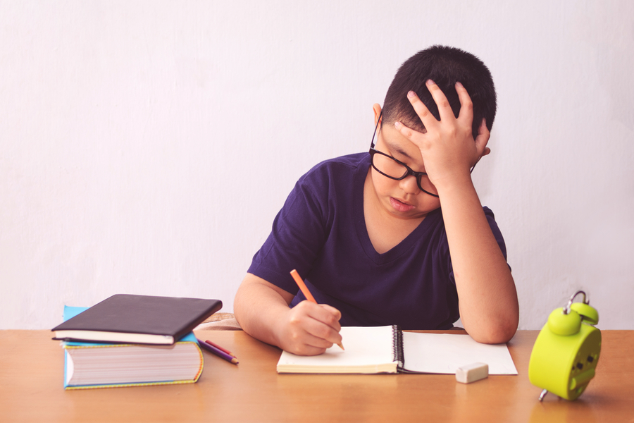 Boy looking stressed while doing homework for maths tuition class