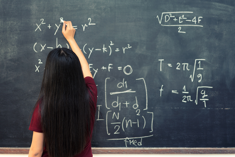 Girl writing on blackboard during maths tuition class
