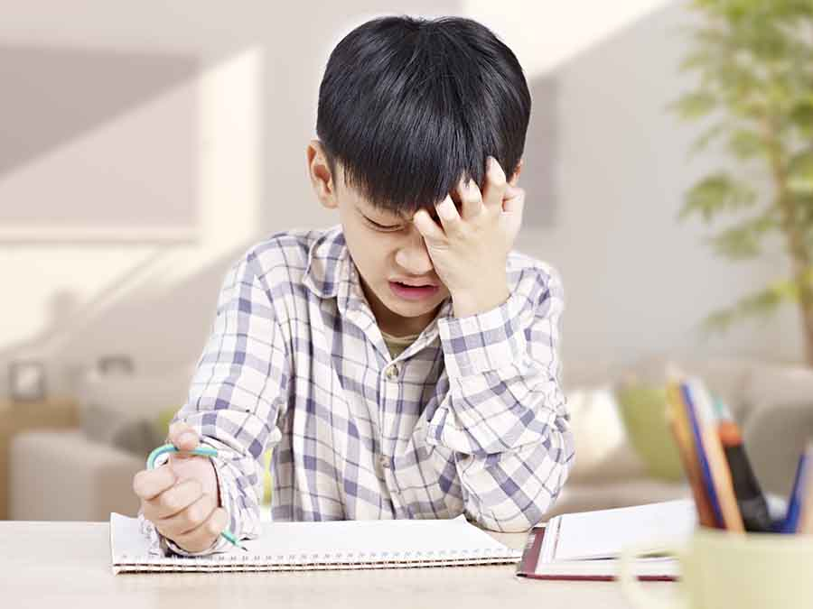 boy stressed out and fustrated by maths question