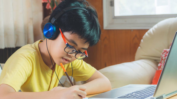 boy learning math online with headset and note taking